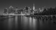 Dramatic, black and white New York City skyline from Brooklyn Bridge Park at night.