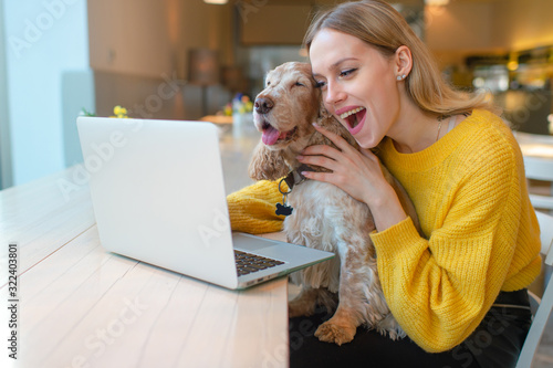 Portrait of beautiful blogger babe with surprised face holding her adorable puppy and using laptop while watching comedy Tablou Canvas