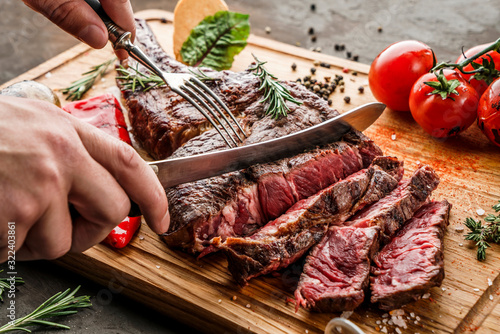 Hands cut grilled tomahawk meat medium rare or rib eye steak on wooden cutting board with grilled vegetables on dark background, close up - 322403861
