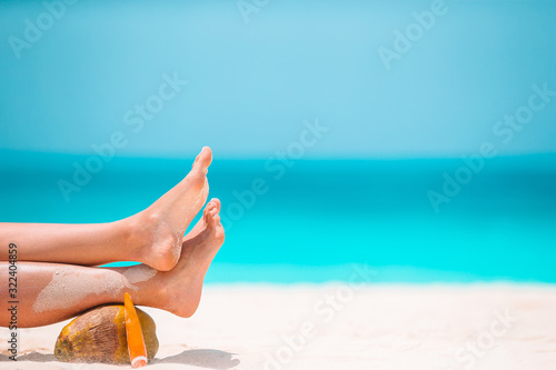 Woman's feet on the white sand beach in shallow water Canvas Print