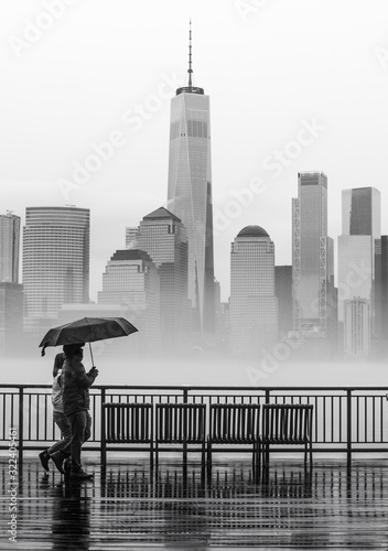 Fototapeta New York   dwie-osoby-chodzace-we-mgle-i-deszczu-z-panorama-nowego-jorku-w-tle