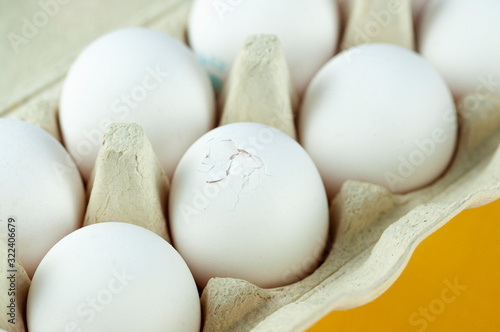 package with a dozen white eggs on a yellow background, one egg broken Canvas Print