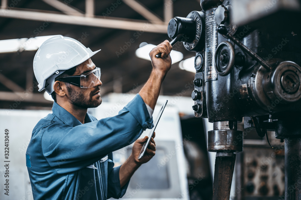 Fototapeta Engineer working at industrial machinery in factory. Manual workers cooperating while measuring a electronic.
