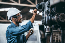 Engineer Working At Industrial Machinery In Factory. Manual Workers Cooperating While Measuring A Electronic.