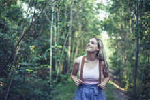 Portrait Of Smiling Young Woman With Backpack In Forest Watching Something