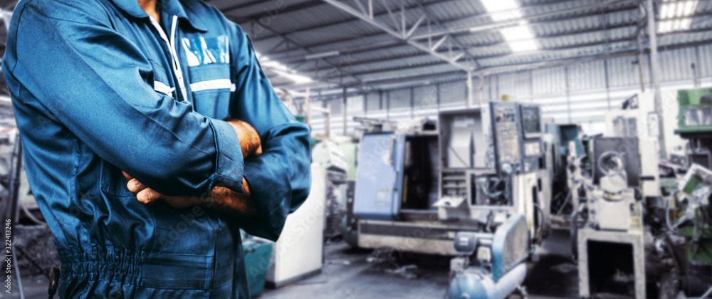 Fototapeta The image Engineer is wearing a uniform safety for industry background. men is standing with arms folded in a storage facility or warehouse.