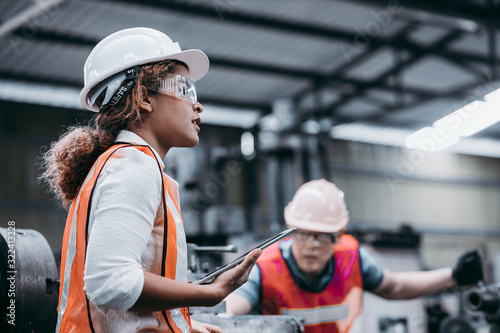 Fotografia Female industrial engineer wearing a white helmet while standing in a heavy indu