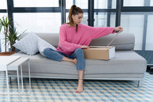 Young Woman Sitting On Couch U...
