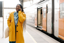 Portrait Of Smiling Young Woman On The Phone Standing On Platform, Barcelona, Spain