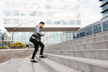 Casual Young Businessman Using Cell Phone In The City Walking Up Stairs