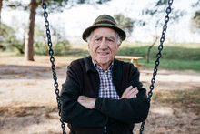 Old Man Sitting On Swing In Park, With Arms Crossed