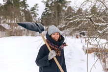 Portrait Of Smiling Woman With Snow Shovel