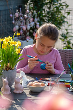 Concentrated Girl Sitting At Garden Table Painting Easter Eggs