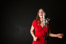 Portrait Of Female Singer With Microphone, Wearing Red Dress