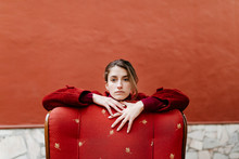 Portrait Of Serious Young Woman Eaning On Back Rest Of Red Lounge Chair