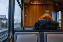 Interior View And Selected Focus View At The Back Of Woman Passenger With Black Fur Hood Of Winter Jacket Inside Vintage Retro Old Wooden Tram Or Train In Germany.