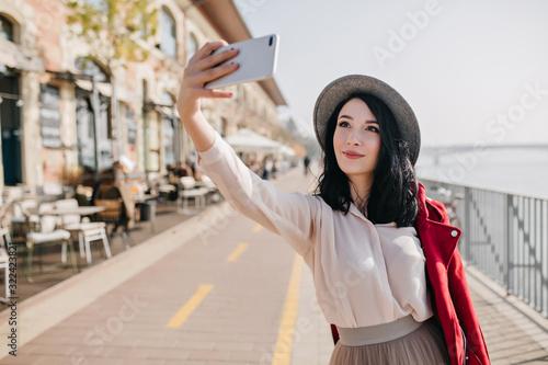 Obraz na plátne Happy dark-haired girl in romantic outfit making selfie near street cafe