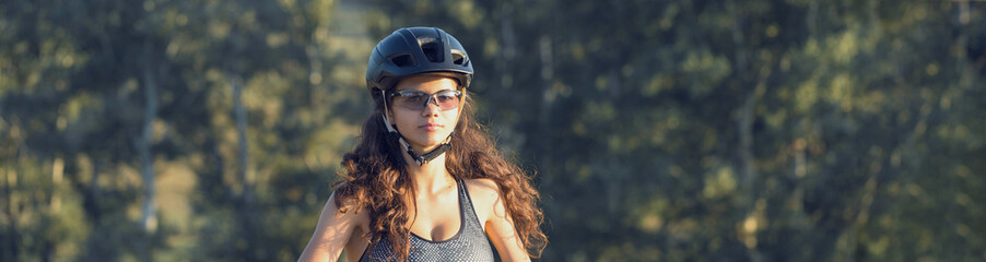 Girl on a mountain bike on offroad, beautiful portrait of a cyclist at sunset, Fitness girl rides a modern carbon fiber mountain bike in sportswear. Close-up portrait of a girl in a helmet and glasses