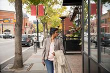 Woman Window Shopping, Walking Along Urban Sidewalk