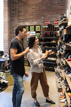Shop Assistant Advising Young Woman Buying Shoes In Shoe Store