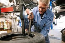 Mechanic Repairing Wheel In Au...
