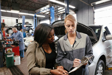 Female Mechanic With Clipboard Talking To Customer With Car In Garage