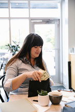 Woman In Cafe Putting Banknotes In Her Purse