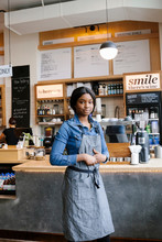 Portrait Of Cafe Worker Standing By Service Counter