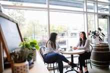 Two Women Sitting In Cafe Talk...