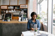 Female Waitress Sitting At Tab...
