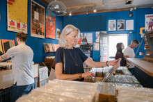 Senior Woman Browsing Vinyl In Independent Record Store