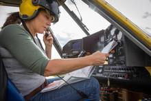Female Pilot Checking Map Inside Crop Sprayer Cockpit