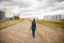 Senior Female Farmer Walking Toward Silos In Farmyard