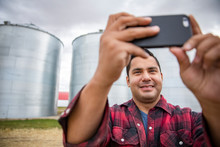 Male Farmer Taking Selfie With Camera Phone In Front Of Silos On Farm