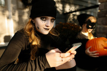 Girl In Halloween Costume Using Smart Phone, Little Sister With Pumpkin In Background