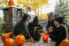 Family With Trick Or Treat Candy Buckets And Carved Pumpkins On Porch