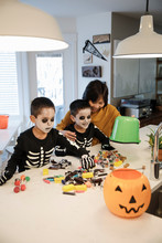 Mother And Sons With Trick Or Treat Candy Buckets On Table