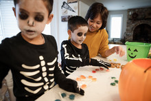 Mother And Sons With Trick Or Treat Candy Bucket On Table