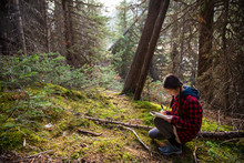 Girl Writing In Journal In Woods