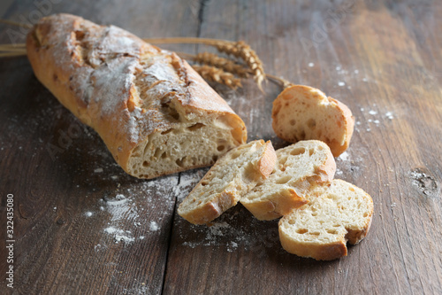 Photo Half sliced baguette or French bread baked with onions on dark rustic wood