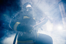 Portrait Of A Female Firefighter While Holding An Axe And Wearing An Oxygen Mask Indoors Surrounded By Smoke.