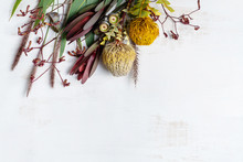 Beautiful Flat Lay Floral Arrangement Of Mostly Australian Native Flowers, Including Protea, Banksia, Kangaroo Paw Eucalyptus Leaves And Gum Nuts On A White Background.
