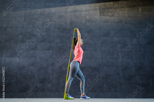 Fototapeta Fit attractive caucasian brunette doing exercises with flexing rope outdoors