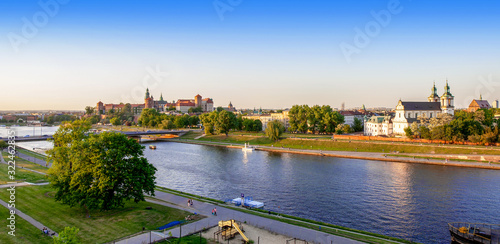 Krakow, Poland. Aerial panorama with Wawel cathedral and castle, Skalka church, Paulinite monastery, Vistula river, bridge, playground, parks and promenades along the riverside. Summer, sunset light
