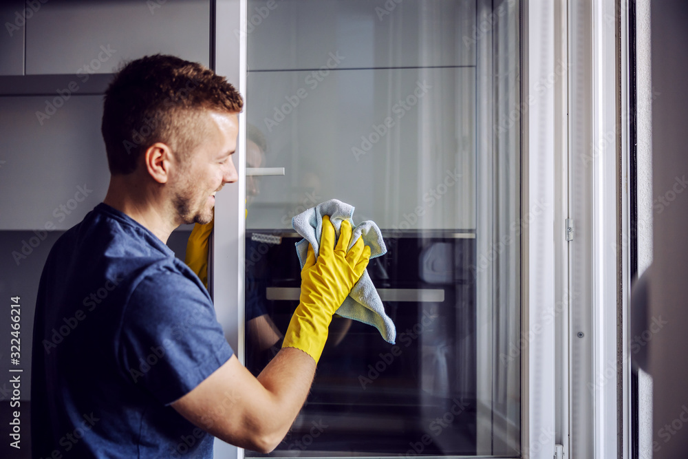 Fototapeta Young bearded smiling positive man with rubber gloves cleaning window with cloth. After rain there is always stains on glass.