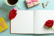 Empty Note Paper With Red Rose Flower, Black Coffee, Gift Boxes On Mint Green Background. Flat Lay, Top View, Copy Space