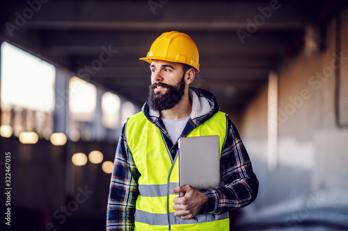 Fototapeta Portrait of highly motivated caucasian hardworking smiling bearded supervisor with helmet on head in vest and with laptop in hands posing on construction site. obraz