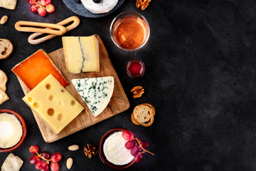 Cheese platter, shot from the top on a black background with copy space. Blue cheese, Brie, Dutch cheese and others with wine