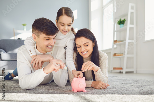 Foto Happy family saves money in a piggy bank pig.