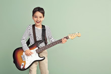 Little Boy Playing Guitar On Color Background